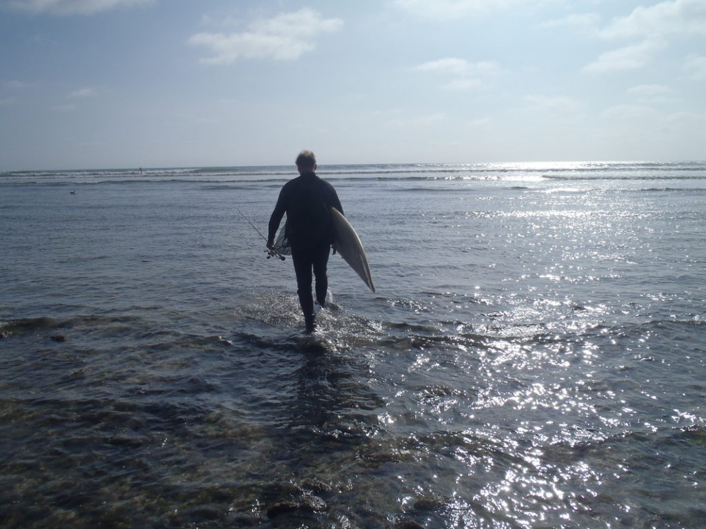Surfer With Board And Fishing Rod